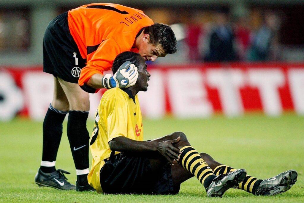 Austria-Torwart Thomas Mandl kümmert sich nach seinem Kreuzbandriss-Tor um den verletzten Otto Addo.