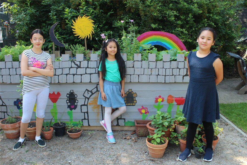Bei den Waldrittern ist selbst Gartenarbeit kreativ: Das Hochbeet haben die am Gartenoase-Projekt teilnehmenden Kinder als eine Burg gestaltet. Zahraa (l.) und die Schwestern Dana und Mona (r.) präsentieren stolz das Ergebnis.