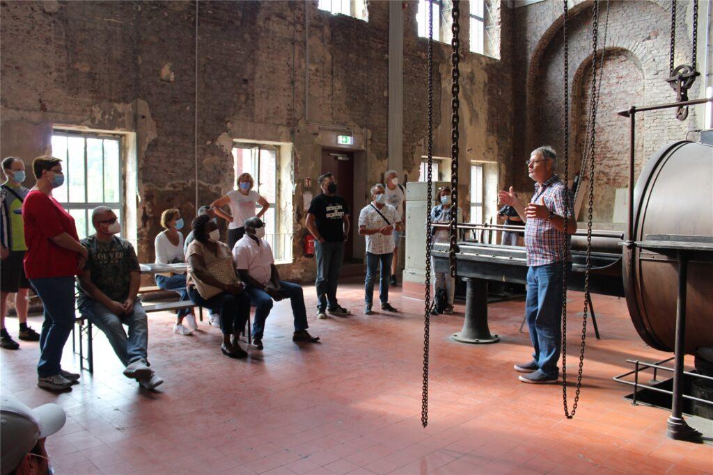 Paul-Walter Georgi (r.) erklärt den Besuchern die Funktionsweise der Dampffördermaschine auf dem Zechengelände Schlägel und Eisen.